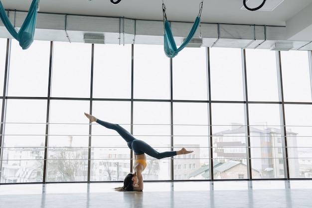 Das junge attraktive mädchen, das eignung tut, trainiert mit yoga auf dem boden. panoramafenster