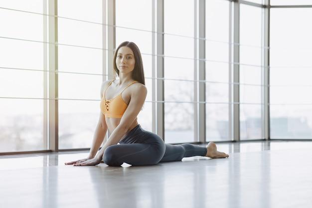 Das junge attraktive mädchen, das eignung tut, trainiert mit yoga auf dem boden