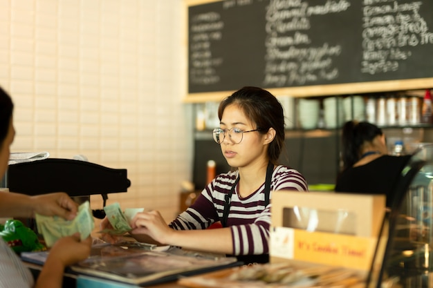 Das junge barista, das geld vom kunden nimmt, zahlen für getränk an der kaffeestube.