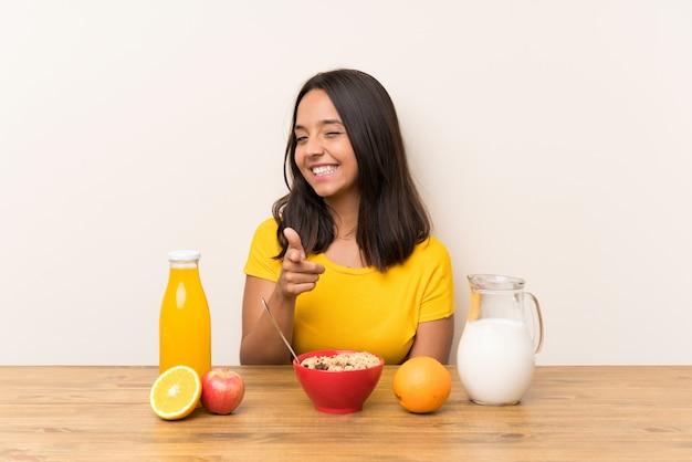 Das junge brunettemädchen, das frühstücksmilch hat, zeigt finger auf sie