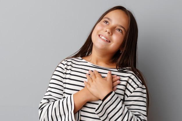 Das junge brunettemädchen, das ihr herz mit ihren händen berührt, überreicht grauen hintergrund
