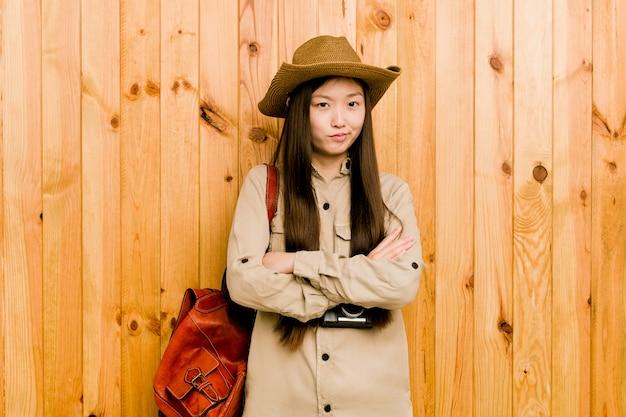 Das junge chinesische die stirn runzelnde gesicht der reisendenfrau im missfallen, hält arme gefaltet.