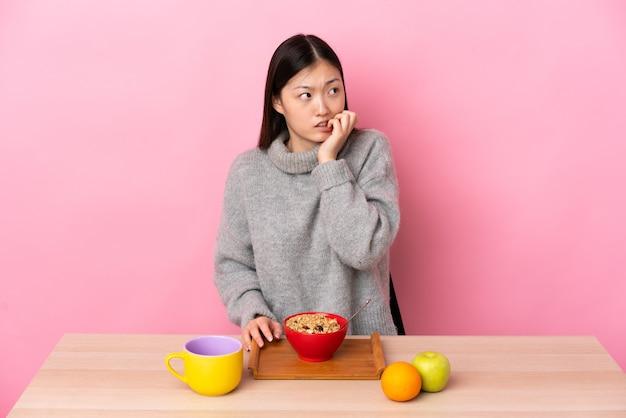 Das junge chinesische mädchen, das in einem tisch frühstückt, ist ein bisschen nervös