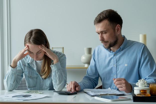 Das junge ehepaar, das am wohnzimmertisch sitzt und papiere studiert, berechnet das familienbudget auf einem taschenrechner