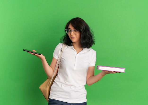 Das junge erfreute hübsche kaukasische schulmädchen, das brille und rückentasche trägt, hält buch und telefon auf grün mit kopienraum