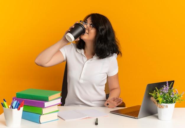 Das junge erfreute hübsche kaukasische schulmädchen, das eine brille trägt, sitzt am schreibtisch mit schulwerkzeugen und trinkt eine tasse kaffee, die auf orange mit kopienraum nach oben schaut
