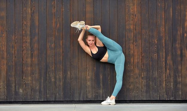Das junge europäische frauensportmodell, das draußen entlang hölzerner wand aufwirft, laufen, springen, rütteln, ausdehnen, tragen im sport schließt, turnschuhe und schwarze spitze