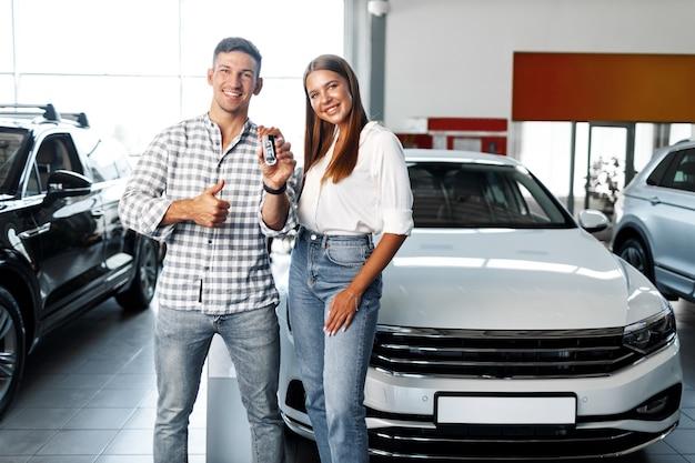 Das junge glückliche paar hat gerade ein neues auto in einem autohaus gekauft