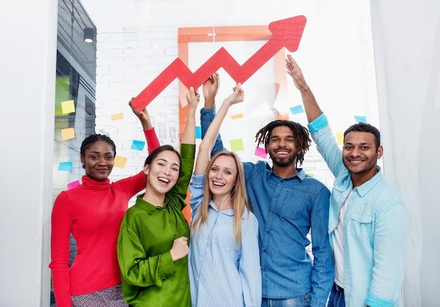 Das junge, glückliche und farbenfrohe geschäftsteam verfügt über ein rotes statistisches pfeilkonzept für erfolg und gewinn