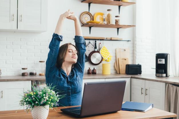 Das junge hübsche schwangere freiberufliche mädchen arbeitet zu hause in der küche im selbstisolationsmodus in quarantäne und wärmt sich vor müdigkeit auf