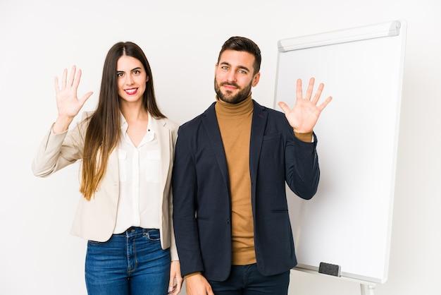 Das junge kaukasische geschäftspaar isolierte lächelnd fröhlich und zeigte nummer fünf mit den fingern.