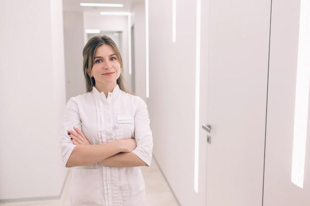 Das junge krankenschwesterporträt gegen die wand des krankenhauses