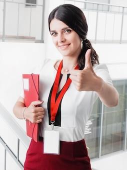 Das junge lächelnde mädchen, das erfolgreiche arbeit gemacht wird, zeigt gesten-großen daumen oben.