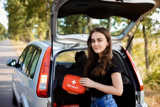 Das junge mädchen, das nahe offener hintertür des silbernen hatchbackautos steht und zeigt erste-hilfe-ausrüstung, die in jedem auto für notfall sein muss