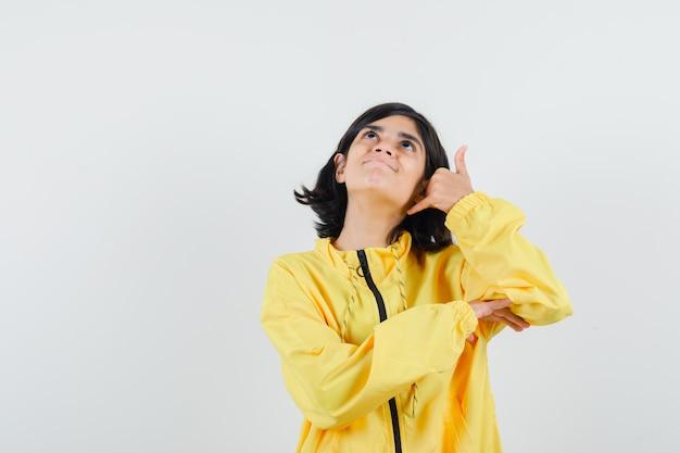 Das junge mädchen, das zeigt, nennt mich geste in der gelben bomberjacke und sieht aufgeregt aus.