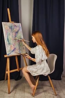 Das junge mädchen des künstlers in einem hellen weißen kleid malt in der werkstatt ein bild auf leinwand. das gesicht ist mit farben befleckt. ein junger student benutzt pinsel, leinwände und staffeleien. kreative arbeit.