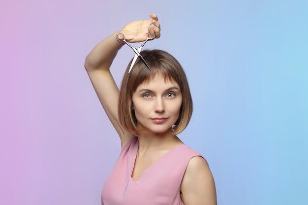 Das junge mädchen hält eine schere in der hand und steht kurz vor einem haarschnitt