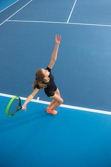 Das junge mädchen in einem geschlossenen tennisplatz mit ball