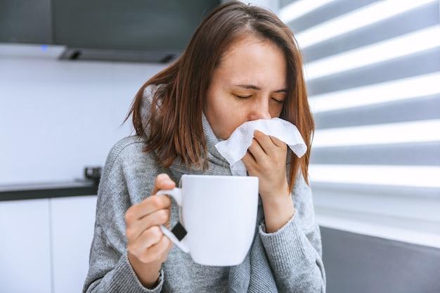 Das junge mädchen ist krank. das mädchen niest in ein taschentuch und hält eine tasse heißen tee in der hand.