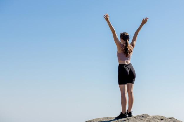 Das junge mädchen oben auf dem berg hob die hände am blauen himmel. die frau kletterte nach oben und genoss ihren erfolg. rückansicht.