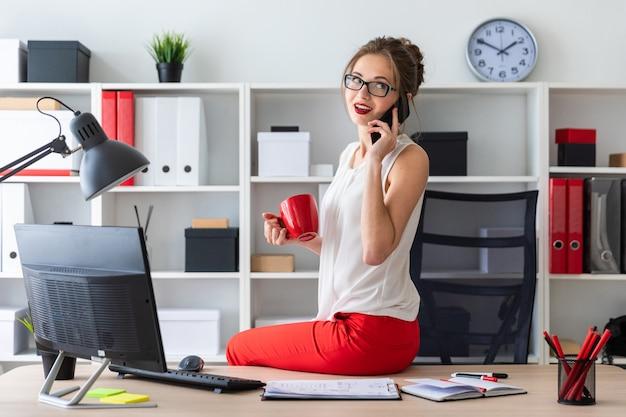 Das junge mädchen setzte sich auf den schreibtisch im büro, hielt eine rote tasse in der hand und telefonierte