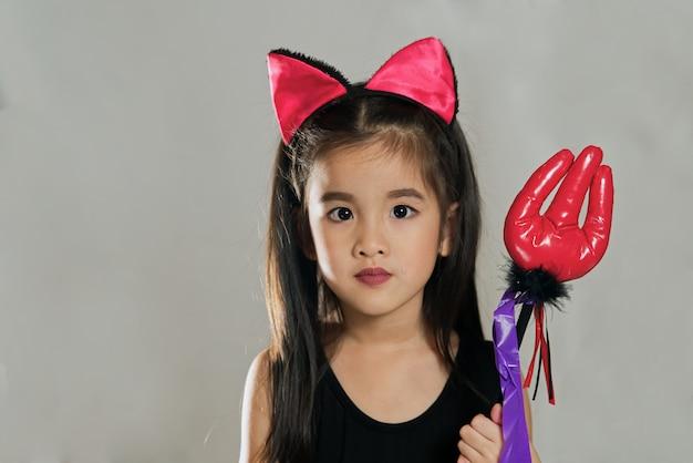 Das junge nette asiatische mädchenkind, das im modekostüm des schwarzen teufels mit den katzenohren ankleidet, hält rote spielzeuggabel in beiden händen