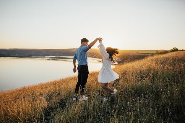 Das junge paar, das hände hält und sich im kreis auf dem see dreht