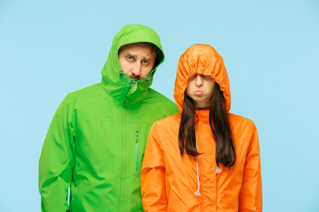 Das junge paar, das im studio in der herbstjacke auf blau isoliert aufwirft. menschliche negative emotionen. konzept des kalten wetters. weibliche und männliche modekonzepte