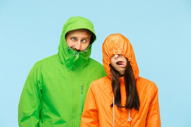 Das junge paar, das im studio in der herbstjacke auf blau lokalisiert aufwirft.