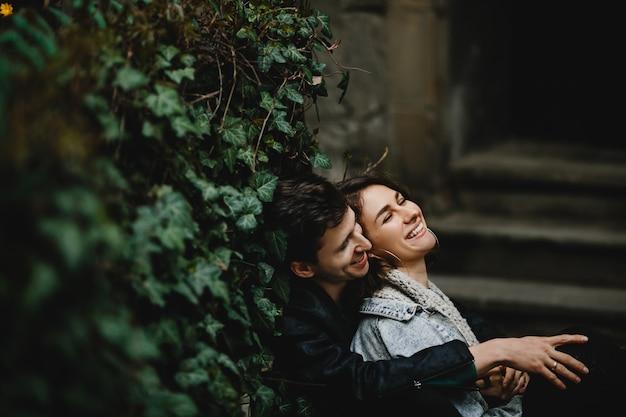 Das junge paar, das umarmt, sitzt nahe grüner wand und lacht