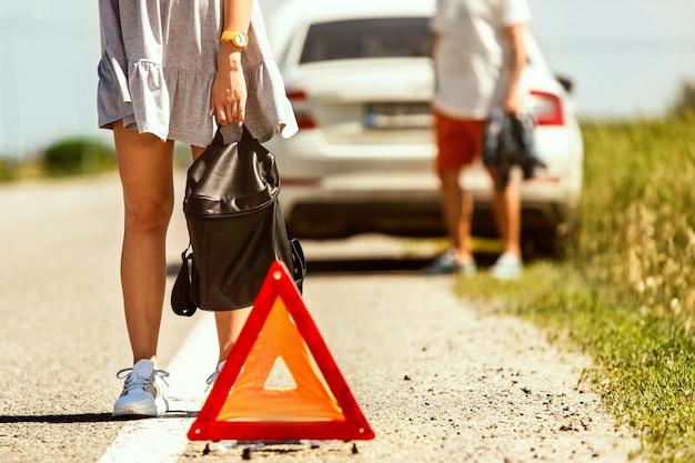 Das junge paar hatte auf dem weg zur ruhe das auto kaputt gemacht. sie versuchen andere fahrer anzuhalten und um hilfe zu bitten oder per anhalter zu fahren. beziehung, probleme auf der straße, urlaub.