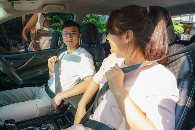 Das junge paar schnallt sich aus sicherheitsgründen vor dem roadtrip in seinem brandneuen auto an.