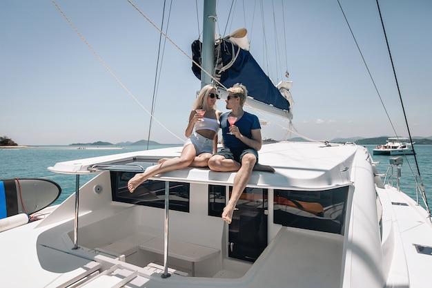 Das junge paar sitzt auf dem dach seiner riesigen weißen laxury-yacht, schaut sich an und trinkt einen cocktail.