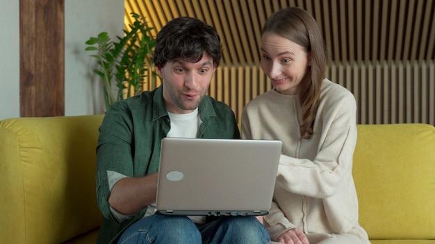 Das junge paar sitzt auf einem gemütlichen gelben sofa, schaut auf einen laptop-bildschirm, gewinnt triumphierend die lotterie online und umarmt sich