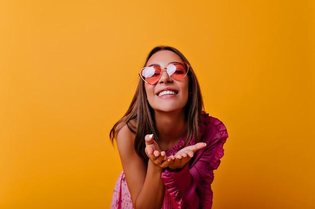 Das junge, schelmische mädchen in der rosa sonnenbrille strahlt vor glück und sendet einen luftkuss. nahes porträt der niedlichen braunhaarigen frau