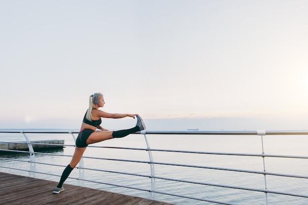 Das junge schöne athletische mädchen mit langen blonden haaren in kopfhörern, die musik hören und sich bei sonnenaufgang über dem meer strecken?
