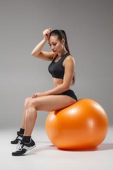 Das junge, schöne sportmädchen, das übungen auf einem fitball im fitnessstudio auf grauem hintergrund macht