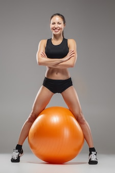 Das junge, schöne sportmädchen macht übungen auf einem fitball