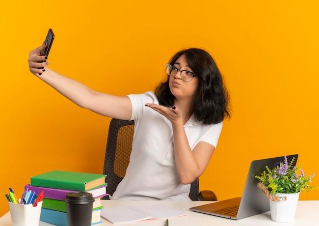 Das junge selbstbewusste hübsche kaukasische schulmädchen, das eine brille trägt, sitzt am schreibtisch mit schulwerkzeugen und schaut auf das telefon, das einen kuss mit der hand auf orange mit kopienraum sendet