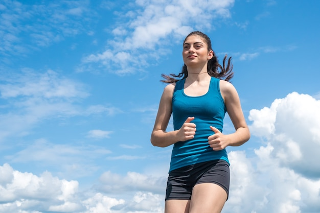 Das junge sportmädchen läuft vom blauen himmel weiter.