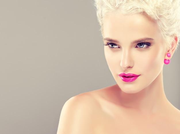 Das junge stilvolle blonde mädchen mit dem trendigen kurzen haarschnitt auf dem kopf demonstriert modisches, helles make-up mit lebhaftem rosa lippenstift. friseurkunst, haarpflege und make-up.