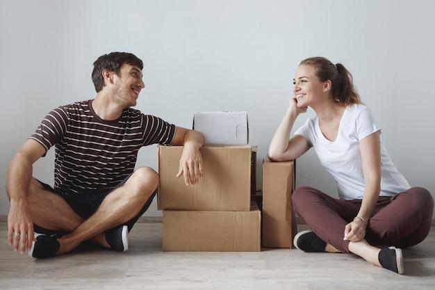 Das junge süße paar, das gerade geheiratet hat und auf dem boden in einer neuen wohnung nach der reparatur zwischen den pappkartons sitzt, ist glücklich und lächelt.