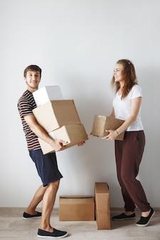Das junge süße paar, das gerade in einer neuen wohnung nach der reparatur zwischen den pappkartons geheiratet hat, ist glücklich und lächelt.
