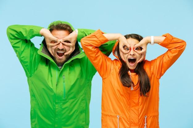 Das junge überraschte paar im studio in herbstjacken isoliert auf blau. menschliche glückliche positive emotionen. konzept des kalten wetters. weibliche und männliche modekonzepte