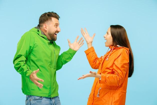 Das junge überraschte paar im studio in herbstjacken isoliert auf blau. menschliche negative emotionen. konzept des kalten wetters. weibliche und männliche modekonzepte
