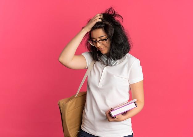 Das junge verärgerte hübsche kaukasische schulmädchen mit kopfhörern am hals, das brille und rückentasche trägt, hält kopf, der unten schaut und bücher auf rosa mit kopienraum hält