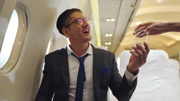 Das kabinenpersonal versorgt den passagier im flugzeug mit wasser. konzept für flugverkehr und tourismus.
