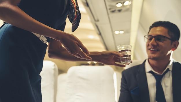 Das kabinenpersonal versorgt den passagier im flugzeug mit wasser