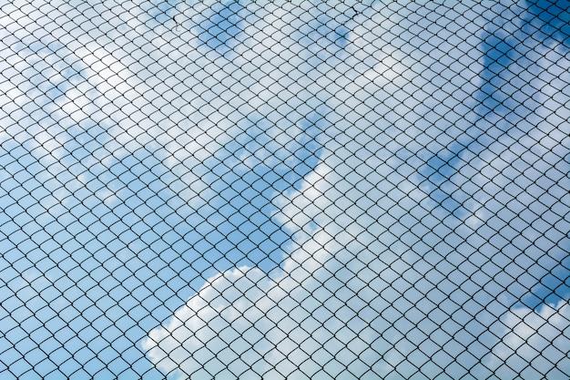 Das käfigmetallnetz auf hintergrund des blauen himmels - kopieren sie art