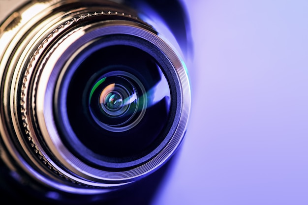 Das kameraobjektiv mit lila hintergrundbeleuchtung. optik. horizontales foto